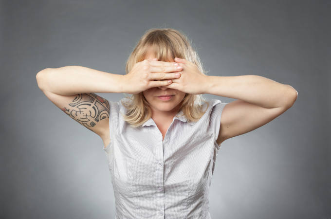 Young woman portraits on grey background, covering her eyes