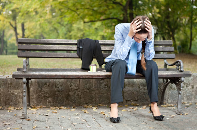 worried businesswoman sitting on bench in park