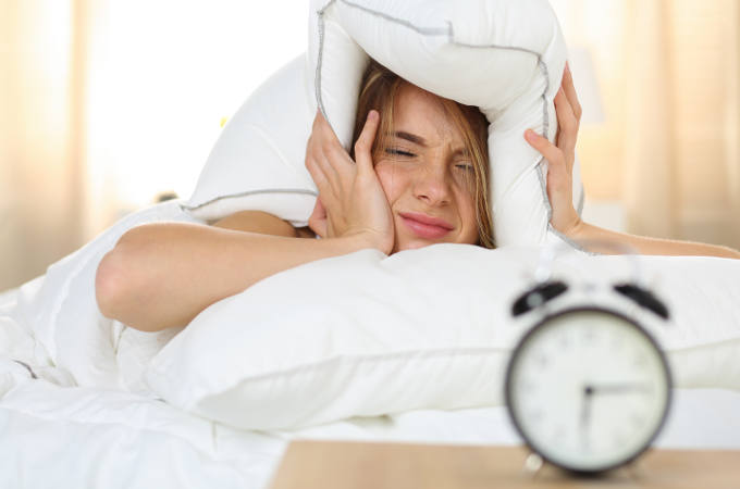 Young Woman Trying to Ignore Alarm